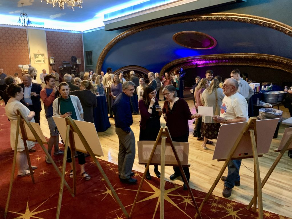 people stand in front of easels with canvas on them and around a large room with curved blue ceiling