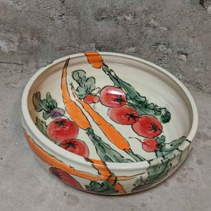 A hand-made ceramic bowl with hand-painted tomatoes and carrots decorating the inside and outside