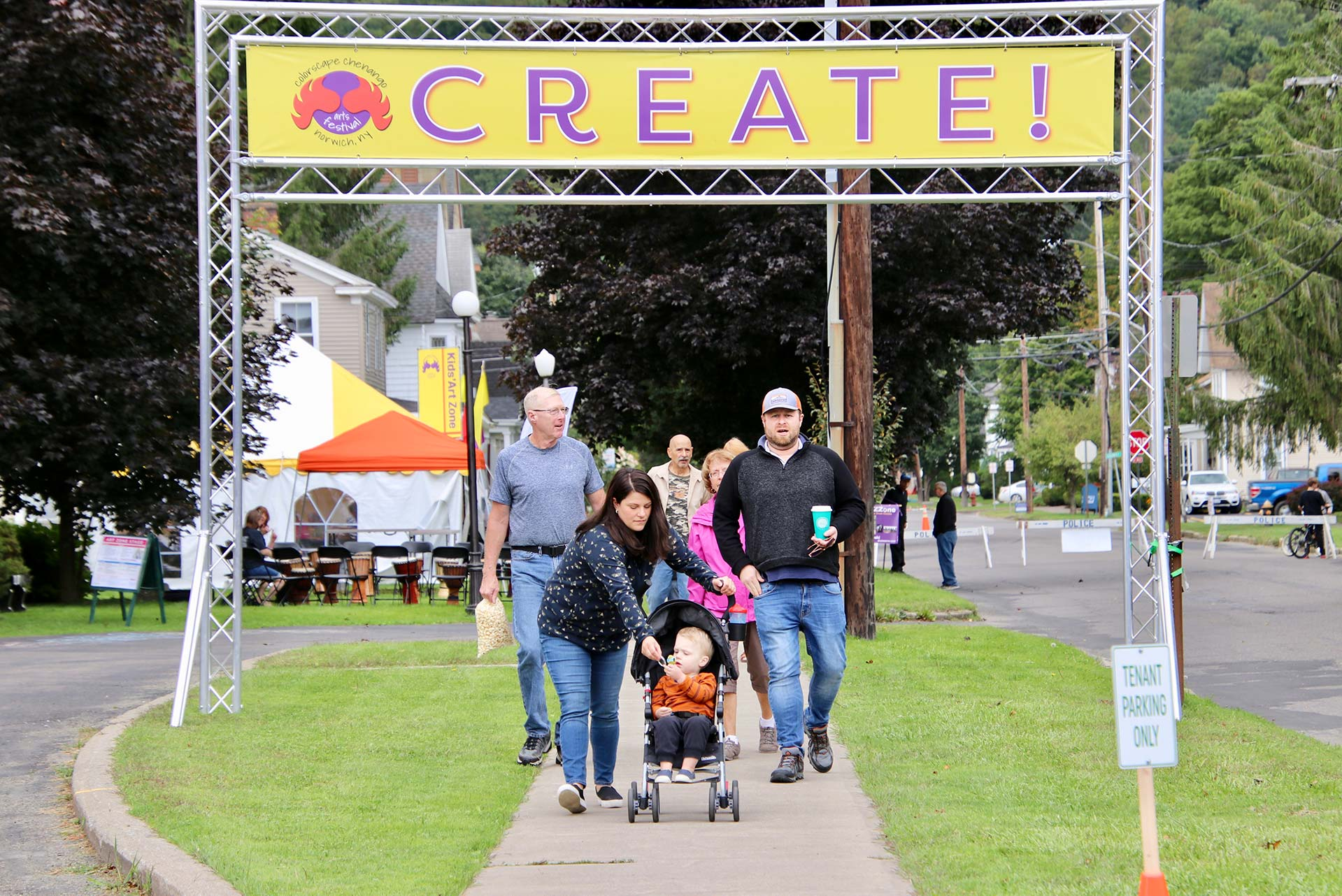 A family with young children walks under a large banner that says CREATE! at the Colorscape Chenango Arts Festival