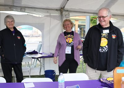 Three volunteers smile in the Volunteer tent at the Colorscape Chenango Arts Festival