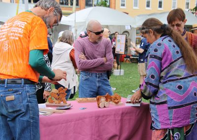 Festival attendees admire an artist's wooden toys at the Colorscape Chenango Arts Festival