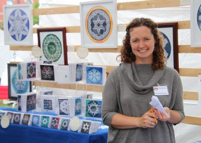 A young woman cuts out a paper snowflake in her artist booth at the Colorscape Chenango Arts Festival