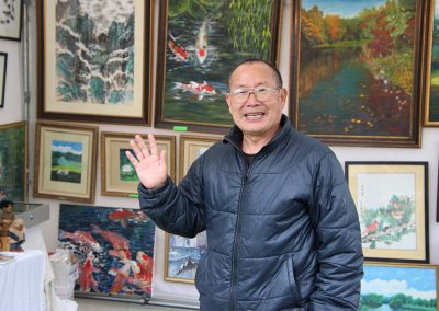 A man smiles next to his detailed watercolor paintings showing koi fish and natural landscapes