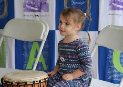 A young girl sits next to a bongo drum at the Colorscape Chenango Arts Festival