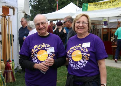 Two volunteers smile near artist booths at the Colorscape Chenango Arts Festival