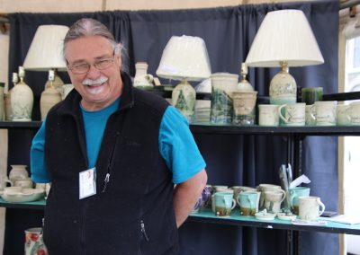 An artist smiles in his booth next to shelves of white and blue pottery at the Colorscape Chenango Arts Festival