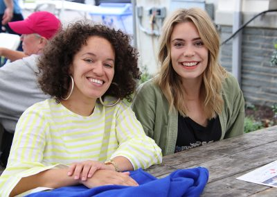 Two festival attendees smile at a table during the Colorscape Chenango Arts Festival