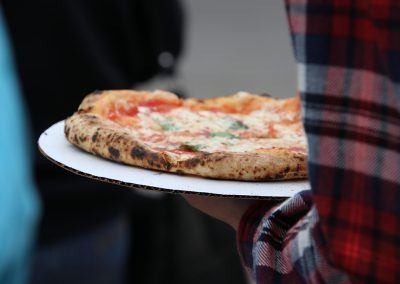 A festival attendee holds a plate of cheese pizza at the Colorscape Chenango Arts Festival