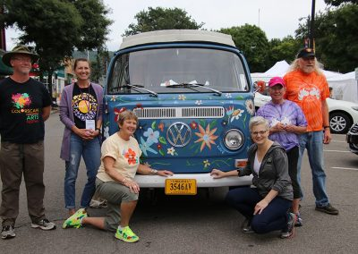 Volunteers and festival attendees pose by a painted VW Bus at the Colorscape Chenango Arts Festival