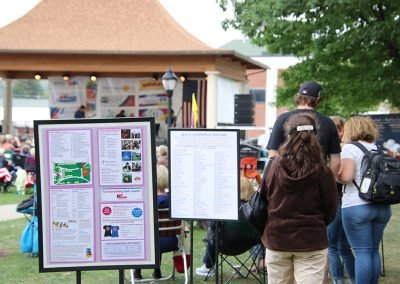Festival attendees walk past informational signs at the Colorscape Chenango Arts Festival