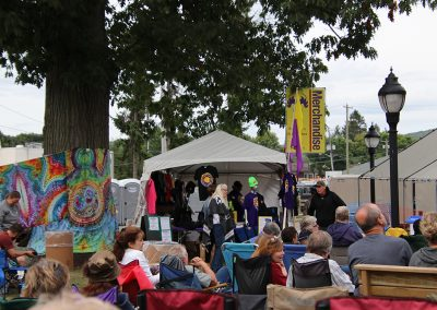 Festival attendees gather outside the Merchandise tent to listen to music at the Colorscape Chenango Arts Festival