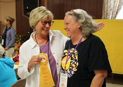 A volunteer and artist embrace, holding a yellow ribbon, at the Colorscape Chenango Arts Festival artist breakfast