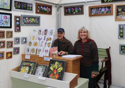 Two vendors smile in their booth filled with vibrant flower art at the Colorscape Chenango Arts Festival