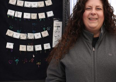 An artist poses with her jewelry at the Colorscape Chenango Arts Festival