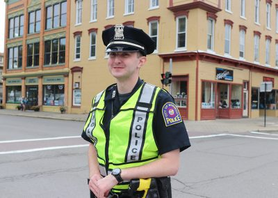 A young police officer smiles and helps direct traffic at the Colorscape Chenango Arts Festival