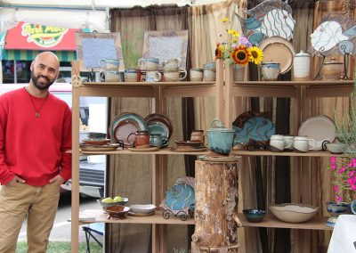 A young man poses next to shelves of pottery in his booth at the Colorscape Chenango Arts Festival
