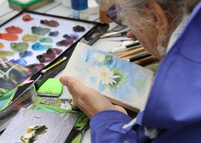 A woman hand-paints a flower on canvas with a large palette of colorful paints in the background