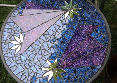 A detailed glass mosaic table glimmers in the sun at the Colorscape Chenango Arts Festival
