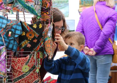 A young child looks at hand-crafted bags at the Colorscape Chenango Arts Festival