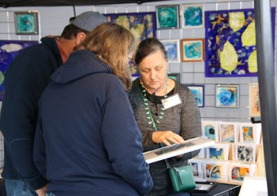 An artist shows her work to festival goers in her booth at the Colorscape Chenango Arts Festival