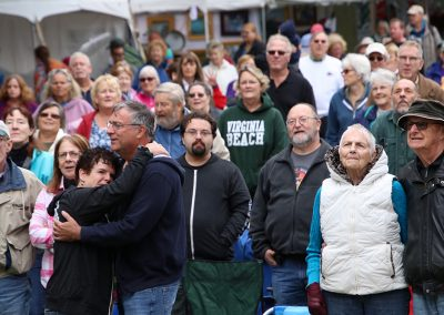 A large crowd smiles as they listen to music at the Colorscape Chenango Arts Festival