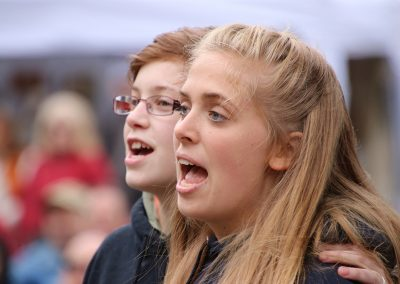 Two young adults sing along to music at the Colorscape Chenango Arts Festival