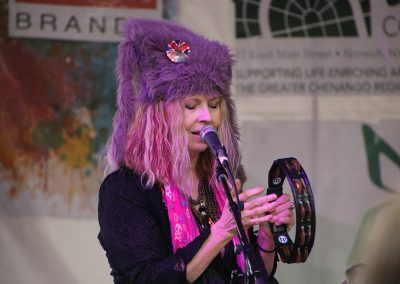 A woman wearing a purple fur hat and bright pink scarf plays the tambourine at the Colorscape Chenango Arts Festival