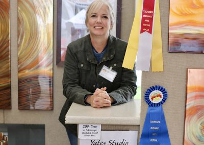 Yates Studio artist, from McDonough, NY smiles next to award ribbons in her booth at the Colorscape Chenango Arts Festival