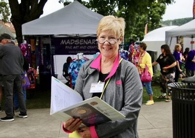 A judge smiles with her binder while visiting artist booths at the Colorscape Chenango Arts Festival