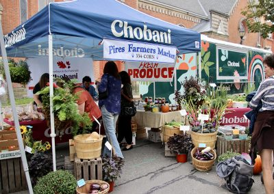 Attendees line up to visit the Chobani tent, which is surrounded by fresh produce, at the Colorscape Chenango Arts Festival