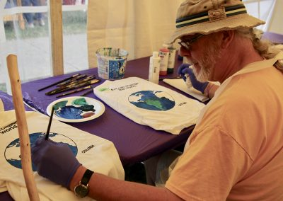 A man paints a t-shirt with a picture of the Earth on it