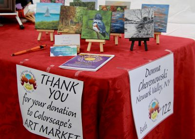 """A collection of small square paintings sit on a table with a red table cloth and a sign that says """"thank you for your donation to Colorscape's Art Market."""" Another sign says, """"Donna Cherenowski, Newark Valley, NY, Booth #122"""""""