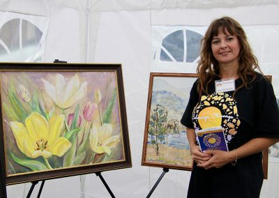 An artist poses next to two large paintings in her booth at the Colorscape Chenango Arts Festival