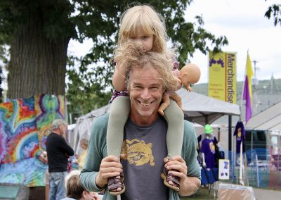 A man smiles while holding a young child on his shoulders at the Colorscape Chenango Arts Festival