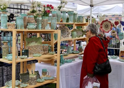 A woman admires detailed imprinted pottery at the Colorscape Chenango Arts Festival