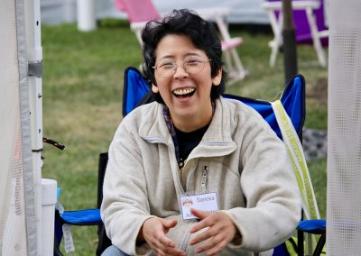 An artist smiles while sitting outside their booth at the Colorscape Chenango Arts Festival