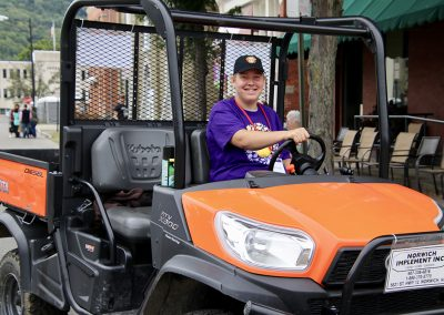 A volunteer smiles as they drive a Kubota vehicle at the Colorscape Chenango Arts Festival