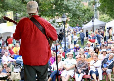 A guitarist wearing a bright red shirt and backwards hat faces a large crowd at the Colorscape Chenango Arts Festival