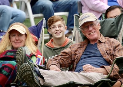 A family smiles as they watch performers at the Colorscape Chenango Arts Festival