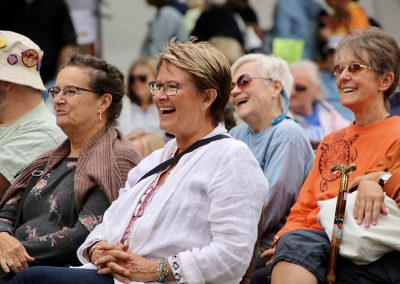 A group of seated attendees smile as they listen to performers at the Colorscape Chenango Arts Festival