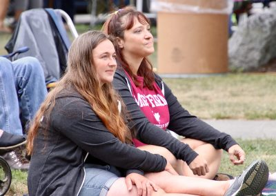 Two young women sit on the lawn watching performers at the Colorscape Chenango Arts Festival