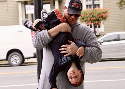 A dad dangles his child upside down, smiling, at the Colorscape Chenango Arts Festival