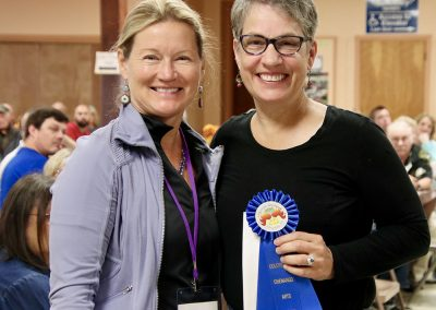 A volunteer and artist pose with a blue ribbon at the Colorscape Chenango Arts Festival artist breakfast