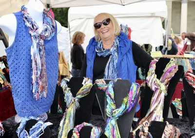 A woman smiles next to brightly colored scarves in her artist booth