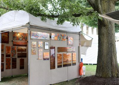 An artist booth with fired copper artwork hanging inside and outside