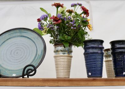 A hand-made ceramic vase holds brightly colored flowers