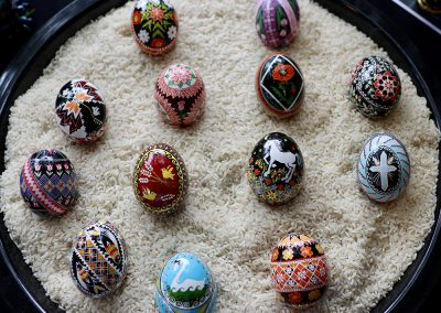 Detailed and vibrant pysanky eggs sit in a bowl of rice