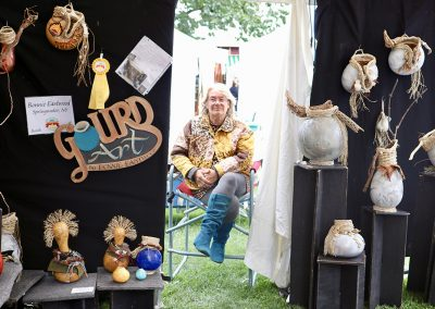 An artist sits in a booth filled with sculptures and vases at the Colorscape Chenango Arts Festival