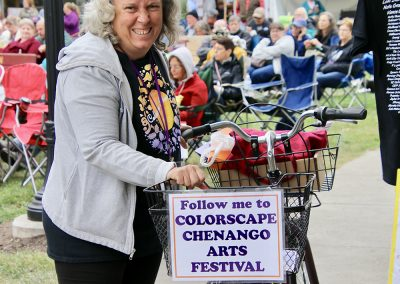 """A volunteer holds a bicycle with a basket and a sign that says """"follow me to Colorscape Chenango Arts Festival"""""""