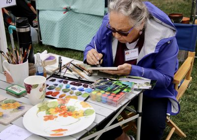 A woman hand-paints a small canvas using a palette filled with colorful paints at the Colorscape Chenango Arts Festival